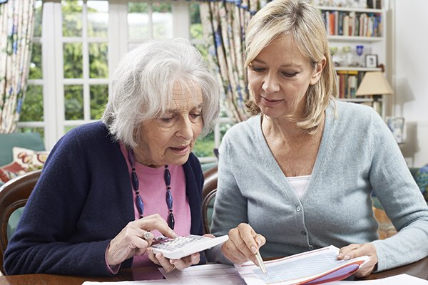 Mature Woman Helping Senior Neighbor With Home Finances