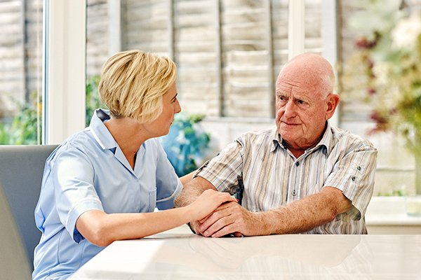 Depressed senior man sitting with female carer