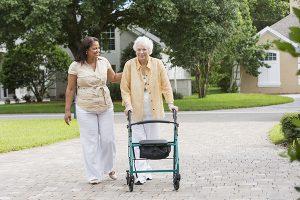caregiver assisting senior using walker outside
