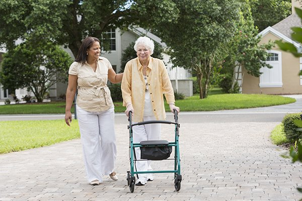 caregiver assisting senior using walker outside