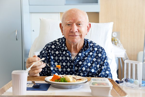 senior man eating meal in hospital bed
