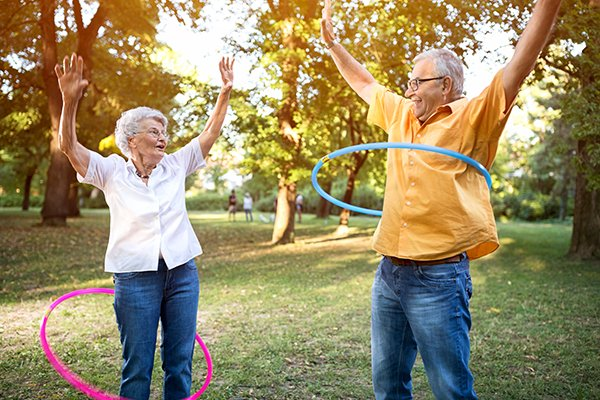 Happy and funny senior couple playing hulahoop in park