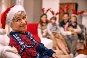 A happy grandmother with her family on Christmas Eve - signs senior care is needed