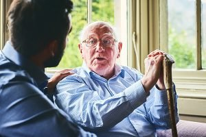 Elderly man with walking stick talking to doctor at home
