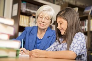 Senior adult teacher, mentor, or tutor assists Latin descent elementary age girl with homework in school classroom or library setting.