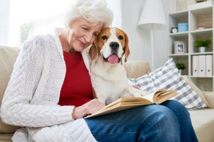 Smiling senior woman reading book with dog