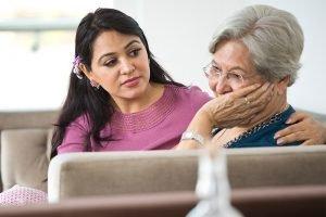caregiver comforting senior with alzeimer's