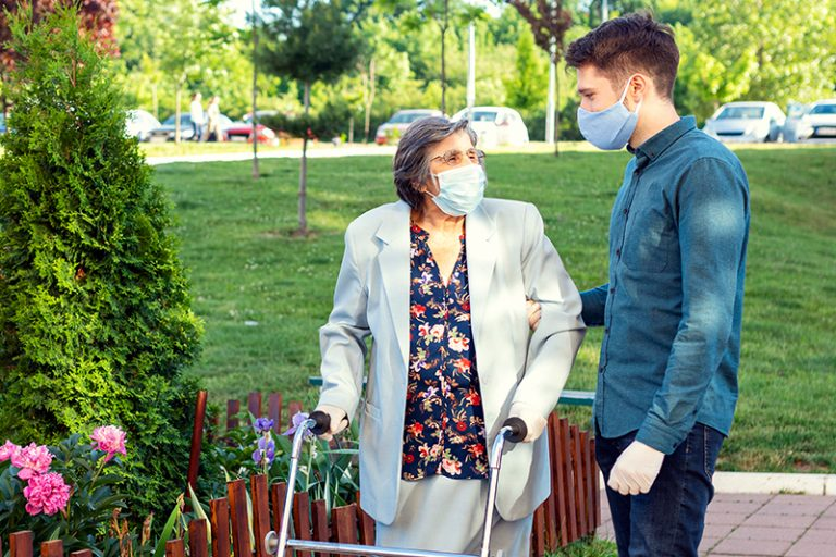 senior caregiver and client wearing protective masks outside