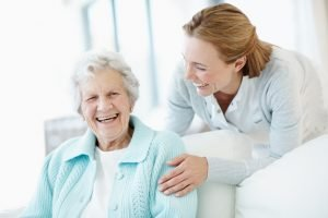 senior woman laughing with family caregiver