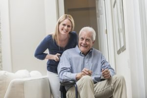 senior being pushed in a wheel chair by family caregiver