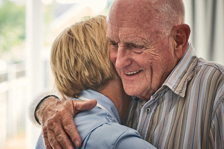 Home carer hugging senior male patient