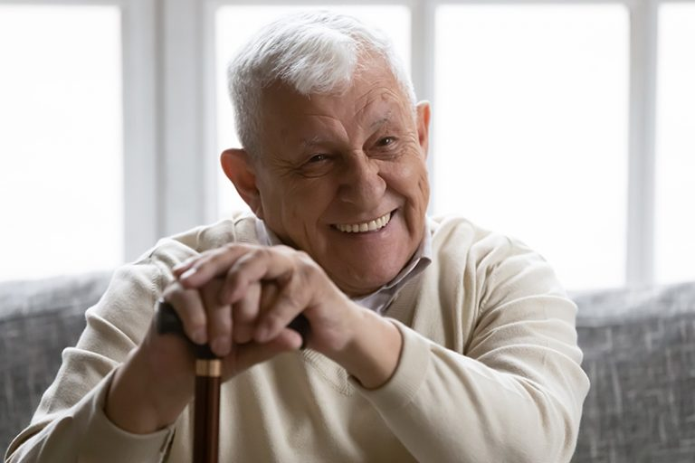 Positive old grandfather holding walking stick resting on couch