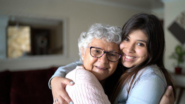 Grandmother hugging her granddaughter at home