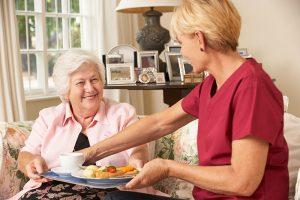 caregiver-serving-senior-woman-a-meal