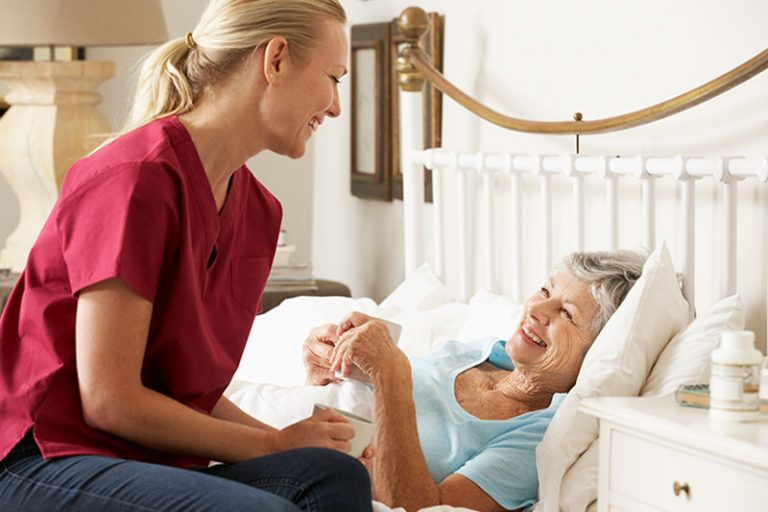 Caregiver talking with happy senior laying in bed