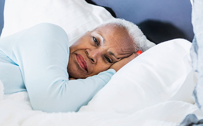 Senior woman with Alzheimer's and sleep problems laying in bed with her eyes open