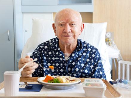 senior man eating meal in hospital bed