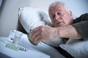 senior man in bed looking at clock